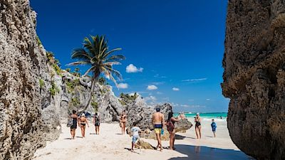 TULUM, MEXICO - FEB 29, 2016 Tourists at the beach under the ruins of the ancient Maya city Tulum, Mexico