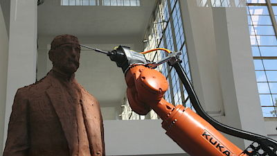 The industrial robot Kuka grinds the statue of President Tomas G. Masaryk, who decorated this area in 1928.